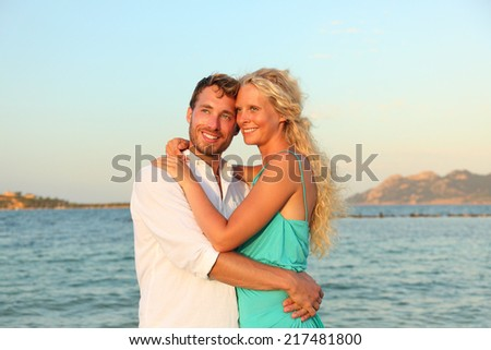 Beach couple romantic in love happy at sunset. Beautiful young couple enjoying summer vacation honeymoon travel holding hands at ocean sea. Caucasian man and woman lovers in their 20s. Mallorca, Spain - stock photo