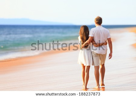 Beach couple walking on romantic travel honeymoon vacation summer holidays romance. Back rear view of casual young happy lovers in full body length on beach.