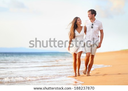 Beach couple walking on romantic travel honeymoon vacation summer holidays romance. Young happy lovers, Asian woman and Caucasian man holding hands embracing outdoors. - stock photo