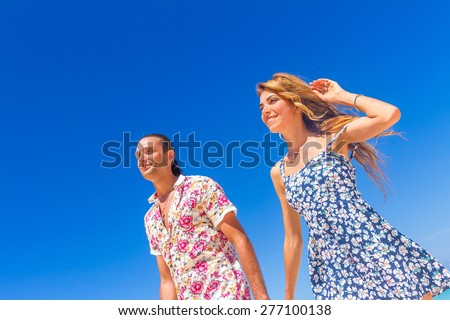 Beach couple walking on romantic travel honeymoon vacation summer holidays romance. Young happy lovers, holding hands embracing outdoors. - stock photo