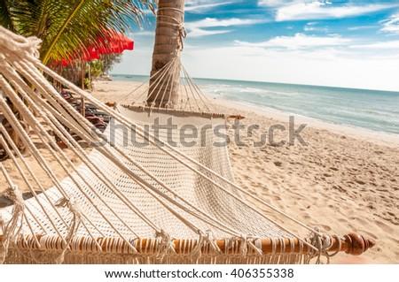 Beach cozy straw hammock on the tropical sunny beach. Summer beach concept. - stock photo