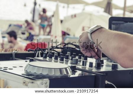 Beach Dj close-up. Summer beach club dj makes party fun for visitors sunbathing, VINTAGE - stock photo