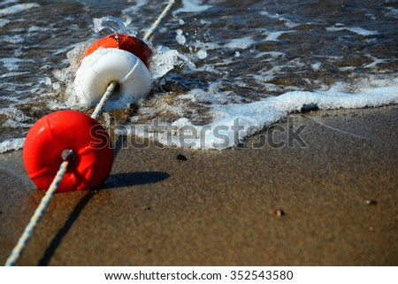 Beach enclosing the float, a sandy pebble beach with incoming wave - stock photo