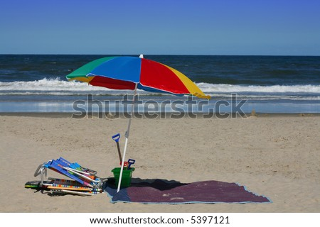Beach Essentials:  A colorful beach umbrella, folding chairs, and beach toys:  all important for a day of fun on the beach.  Vacation concept.