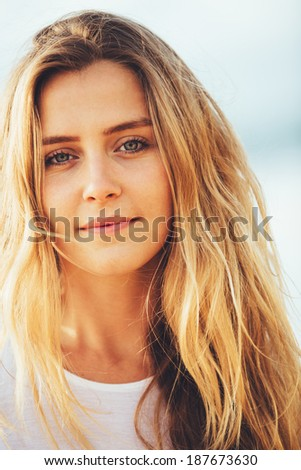 Beach fashion lifestyle, Portrait of beautiful blond girl close-up, wind in her hair.  - stock photo