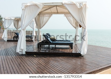 Beach front dual leather relax chairs inside a tent facing the sea, taken on a sunny day - stock photo