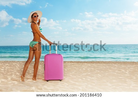 Beach girl with pink luggage near the sea - stock photo