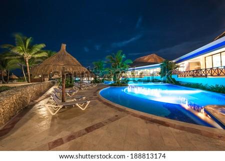 Beach grass umbrella at swimming pool and a restaurant of luxury caribbean resort at night, dawn time. Bahia Principe, Riviera Maya, Mexico. - stock photo
