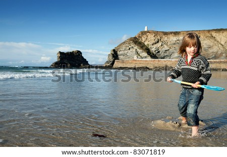 Beach holiday in Cornwall, England. St Agnes coastline with child in water with spade or shovel - stock photo