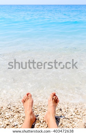 Beach holiday - male feet and summer sea