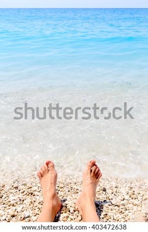 Beach holiday - male feet and summer sea - stock photo