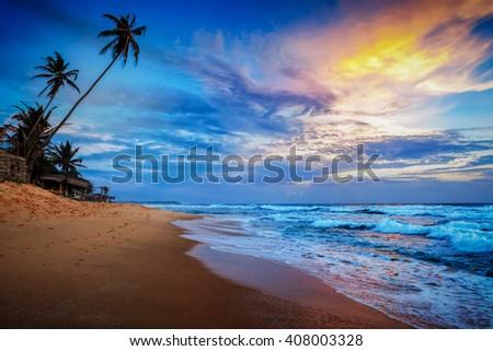 Beach holidays vacation romantic concept background - sunset on tropical beach with dramatic cloud sky. Sri Lanka - stock photo