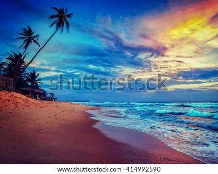 Beach holidays vacation romantic concept background - vintage retro effect filtered hipster style image of sunset on tropical beach with dramatic cloud sky. Sri Lanka - stock photo