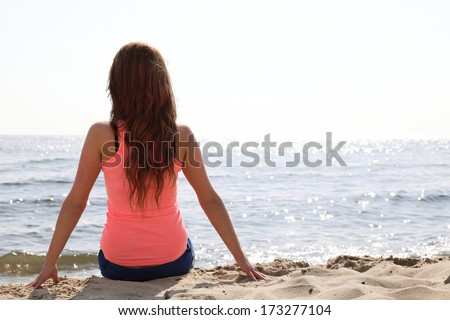 Beach holidays woman back view enjoying summer sun sitting in sand looking happy at copy space. Beautiful young model - stock photo