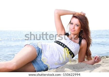 Beach holidays woman enjoying summer sun lie in sand looking happy at copy space. Beautiful young model