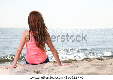 Beach holidays woman enjoying summer sun sitting in sand looking happy at copy space. Beautiful young model