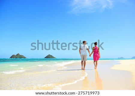 Beach honeymoon couple holding hands walking on white sand beach. Newlyweds happy in love relaxing on summer holidays on Lanikai beach, Oahu, Hawaii, USA with Mokulua Islands. Travel vacation concept.