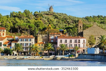 Beach hotel in Collioure village with a windmill at the top of the hill, Roussillon, Vermilion coast, Pyrenees Orientales, France - stock photo