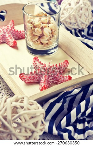 beach house decor, setting summer vacation : Candle in the form of starfish, shells on the wooden background (Toning) - stock photo