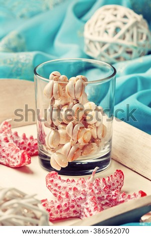 beach house decor, setting summer vacation : Candle in the form of starfish, shells, pareo on the wooden background (Toning) - stock photo
