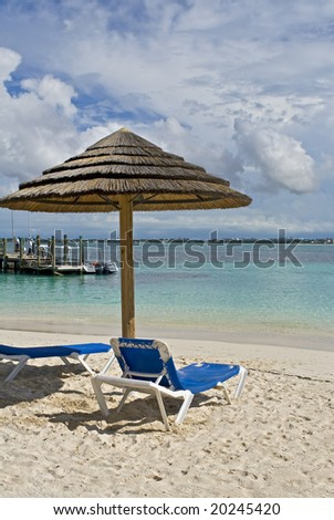 Beach hut with chairs on tropical shoreline at a resort. - stock photo