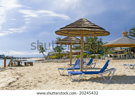 Beach huts and chairs on tropical shoreline of resort.