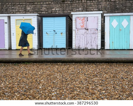 Beach huts in the rain passing woman with wind blown umbrella in front of yellow door