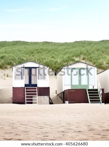 Beach huts or houses and blue sky. Multicolored beach bathing huts with white sand and clear blue sky. Beach scene with copy space. Front view of beach huts in a row.