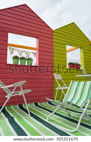 Beach huts with colorful chairs - stock photo