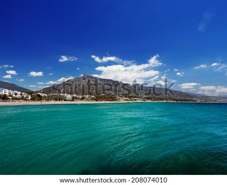 Beach in Puerto Banus, Marbella, Spain. Marbella is a popular holiday destination located on the Costa del Sol in the southern Andalusia, it lies beneath the Cordillera Penibetica mountains  - stock photo