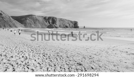 Beach in the Algarve region of Portugal. People swimming and surfing. Aged photo. Black and white. - stock photo