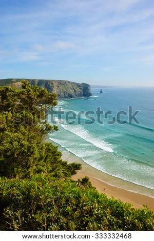 Beach in the Algarve region of Portugal. People swimming and surfing. Pine trees at foreground.  A view from the top. - stock photo