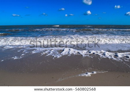 Beach in Tunisia. Mediterranean coast of North Africa. Wind, blue sky, sand and waves