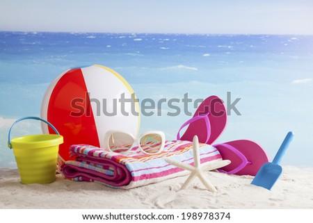Beach items with,flip flops,sunblock,beach ball and sunglasses - stock photo