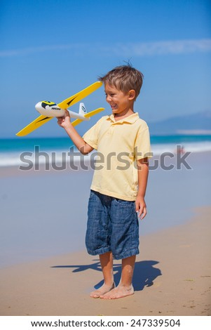 Beach kid boy kite flying outdoor coast ocean - stock photo