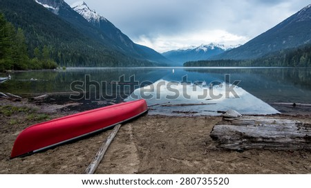 Beach lake shore with a red canoe - stock photo