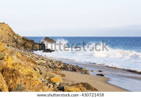 Beach landscape in Malibu. The ocean and waves during strong winds in United States, California. Waves breaking on the rocks. - stock photo