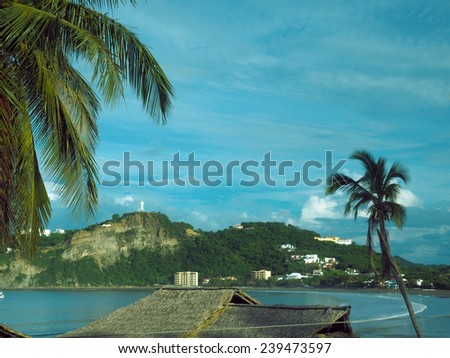 beach landscape resort town  San Juan del Sur Nicaragua with landmark statue Jesus Christ on mountain on Pacific Ocean Central America