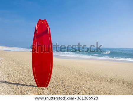 Beach landscape with a red surfboard on the sand - stock photo