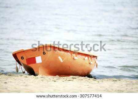 Beach life-saving. Lifeguard rescue equipment orange preserver tool boat, buoyancy aid - stock photo