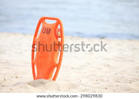 Beach life-saving. Lifeguard rescue equipment orange preserver tool, red plastic buoyancy aid in the sand - stock photo