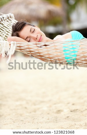 Beach lifestyle woman relaxing in hammock on tropical holidays vacation. Multiethnic Asian Chinese / Caucasian model in bikini on Varadero Beach, Cuba, Caribbean - stock photo