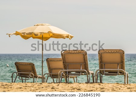 Beach long chairs with umbrella  - stock photo