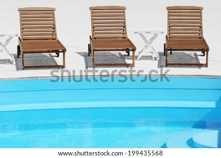 beach lounge chair near the pool on white boards - stock photo