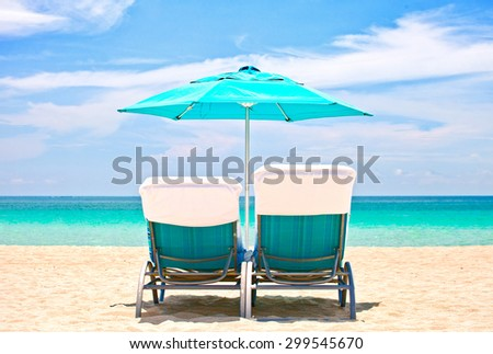 Beach lounge chairs and umbrella in Miami, Florida on a beautiful summer day with ocean and blue sky - stock photo