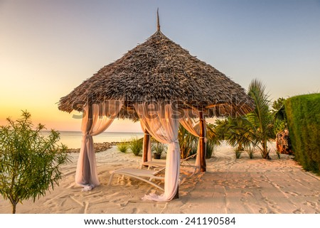 Beach lounge chairs at sunset at the shore of Indian ocean, Zanzibar, Tanzania