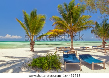 Beach Lounge chairs under palm tree leaves at the shore of Indian ocean, Zanzibar, Tanzania