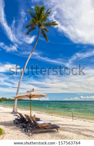 Beach Lounge Chairs with towels under umbrella at the shore of Indian ocean, Zanzibar, Tanzania - stock photo