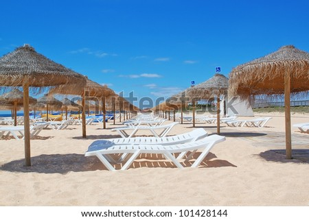 Beach loungers and umbrellas on the sea. Portugal. Vila Moura. - stock photo