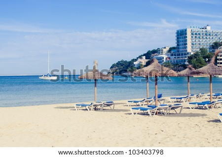 Beach loungers and umbrellas on the sea. Spain. Palma Mallorca - stock photo